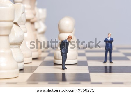 Business figurines placed on chessboard with chess pieces