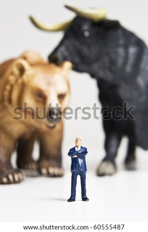 Business figurines placed with bull and bear figurines. - stock photo