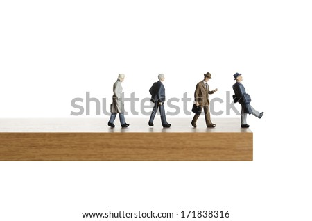 Business figurines walking off a ledge  - stock photo