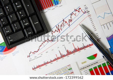 Business finance chart with number pad and silver pen on table.