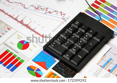 Business finance chart with number pad on table.