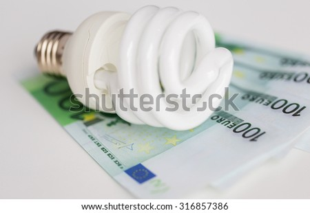 business, finance, energy saving and utilities concept - close up of euro paper money and light bulb on table - stock photo