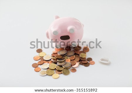business, finance, investment, money saving and budget concept - close up of euro coins and piggy bank on table - stock photo