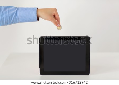 business, finance, investment, money saving and e-commerce concept - close up of hand putting coin into into tablet pc computer with black blank screen