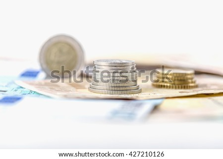 business, finance, saving and cash concept - close up of euro paper money and coins on table - stock photo