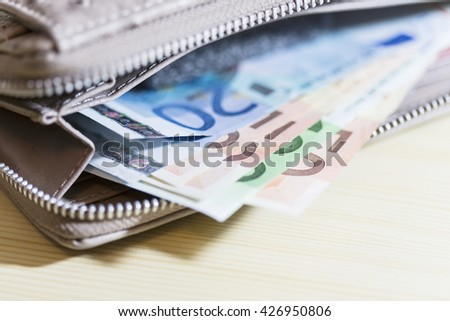 business, finance, saving and cash concept - close up of euro paper money on wallet - stock photo