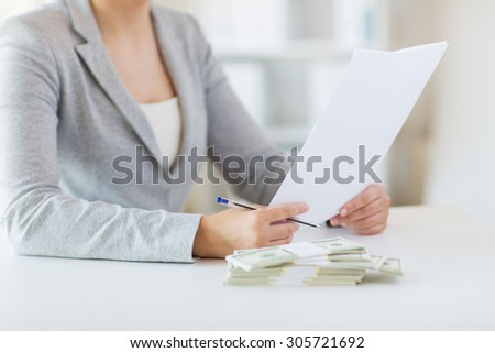business, finance, tax and people concept - close up of woman hands with us dollar money and tax report paper form - stock photo