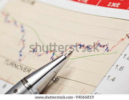 business financial chart with pen - stock photo