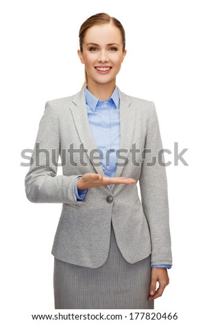 business, future technology and office concept - smiling businesswoman holding something imaginary on palm of her hand - stock photo