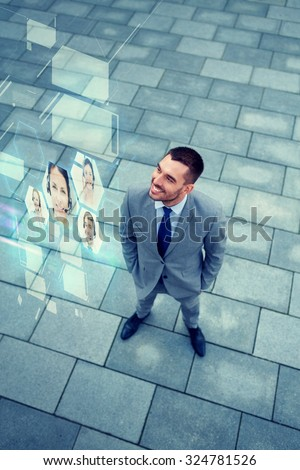 business, future technology and people concept - young smiling businessman with virtual screens using video chat outdoors from top - stock photo