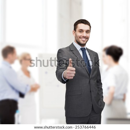 business, gesture and office concept - handsome buisnessman showing thumbs up in office - stock photo