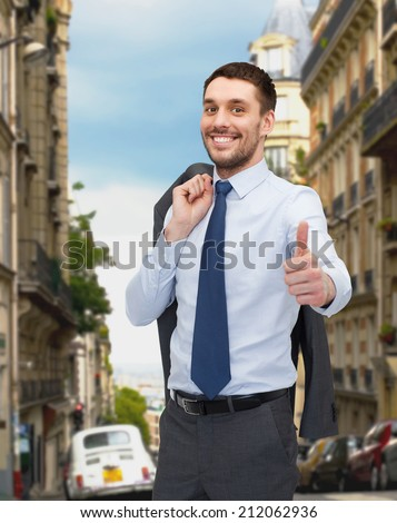 business, gesture and people concept - smiling young and handsome businessman showing thumbs up over old city background