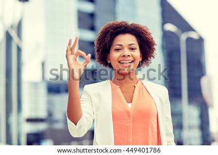 business, gesture and people concept - young smiling african american businesswoman showing ok hand sign in city - stock photo