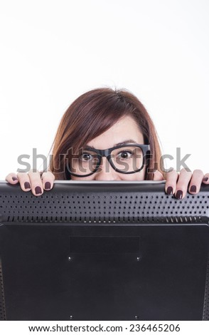 Business girl looking over computer at office wearing black glasses - stock photo