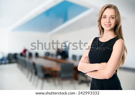 Business girl on the background of the hall for business meetings.