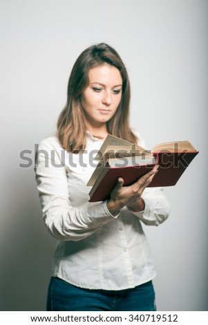 Business girl reading a book. studio photo on a gray background - stock photo