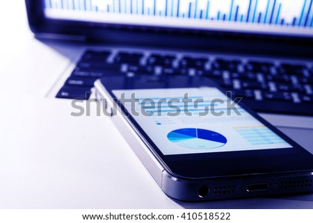 Business graph on smartphone with laptop in modern blue tone style.For business  and financial concept