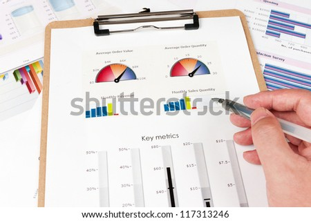 Business graph printed on the white paper with a hand holding a pen on it - stock photo