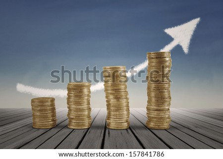 Business graph with arrow and coins showing profits and gains - stock photo