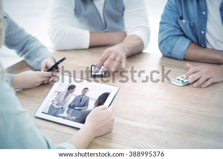 Business graphs against mid section of people using smartphones and digital tablet - stock photo