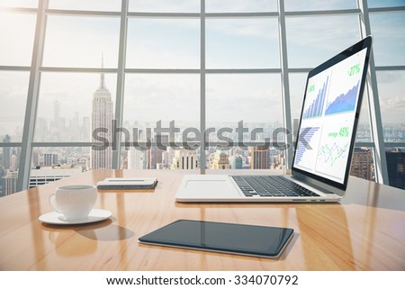 Business graphs on laptop screen, coffee mug, digital tablet on the table in sunny office with windows in floor - stock photo