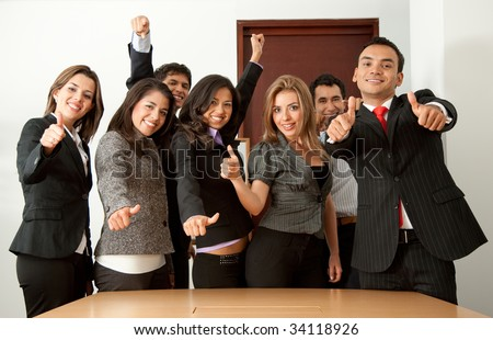 Business group in an office with their thumbs up - stock photo