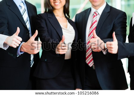 Business - group of businesspeople posing for group photo in office showing thumbs up - stock photo