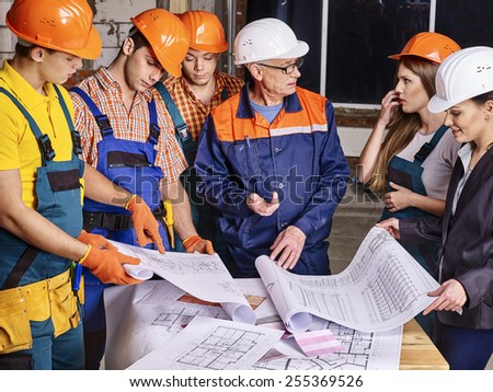 Business group people in builder helmet indoor. Drawings on table - stock photo