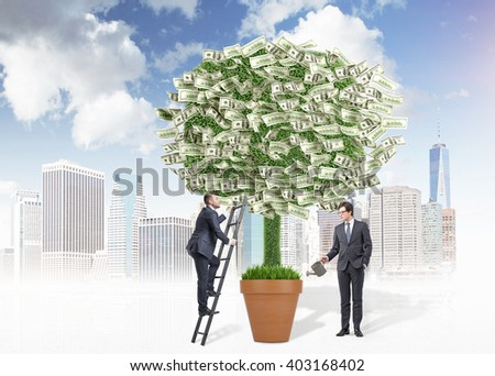 Business growth concept with two businessmen watering and climbing dollar banknote tree on city background - stock photo