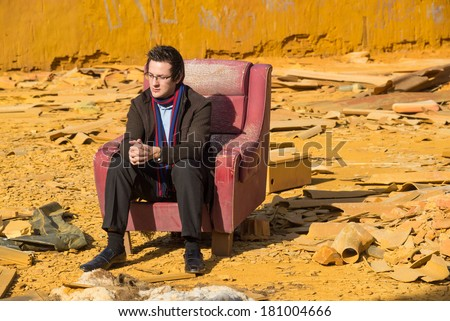 Business guy in trouble among derelict industrial ruin - stock photo