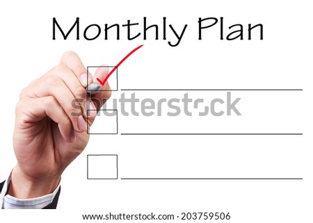 business hand checking the checklist boxes monthly plan by pen on transparent glass