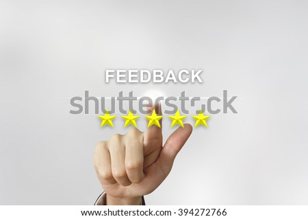 business hand clicking feedback with five stars on screen - stock photo