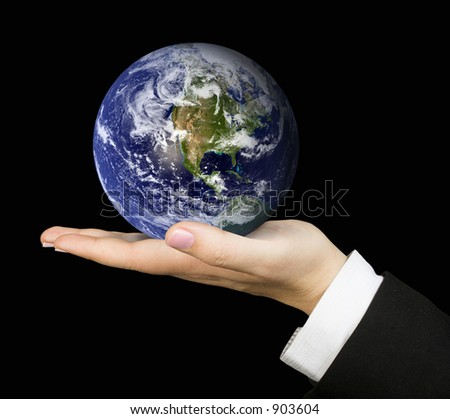business hand holding globe over a black background - stock photo
