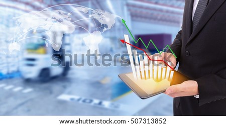 Business hand holding growth chart of transport business on tablet with goods distribution at warehouse,Logistic Import Export  background (Elements of this image furnished by NASA)