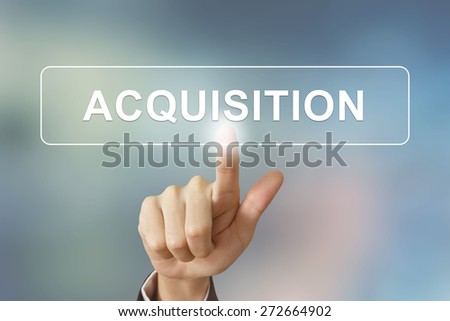 business hand pushing acquisition button on blurred background - stock photo