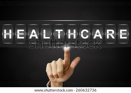 business hand pushing healthcare on Flipboard Display - stock photo