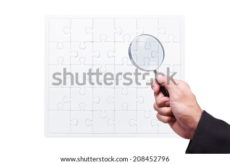 business hand searching something by magnifying glass on white blank jigsaw business concept - stock photo