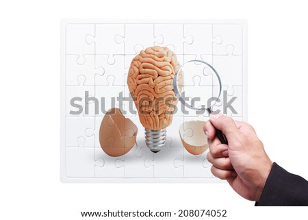 business hand searching success by magnifying glass on jigsaw concept of brain inside a light bulb an egg cracking open on white background with clipping path - stock photo