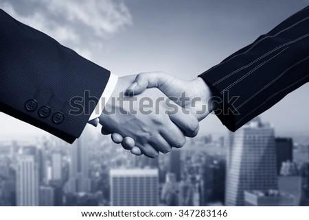business hand shake and Manhattan in background - stock photo