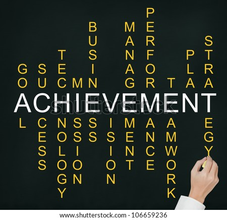 business hand writing business concept by crossword of components which make the achievement such as success, performance, plan, strategy, management, teamwork, etc. - stock photo