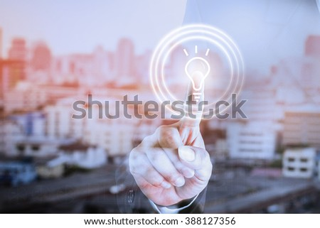 Business hands of a touch screen with a. Concept bulb idea. Can be deployed to create your ad.