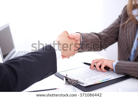 business handshak  sitting at the desk on office background, copy space area at the left upper corner