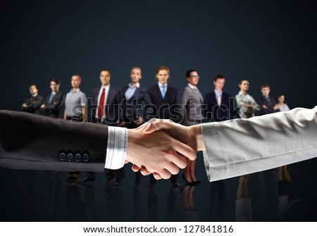 business handshake against black background and standing businesspeople - stock photo