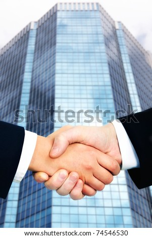 Business handshake against office building - stock photo