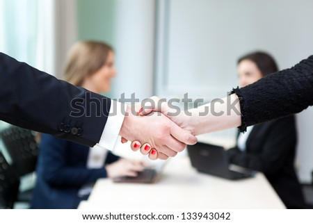 Business handshake and business people at the office - stock photo