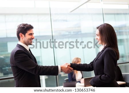 Business handshake at modern office with bussiness people on background