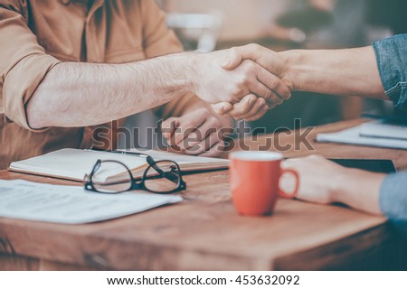 Business handshake. Close-up of two men shaking hands while sitting at the wooden desk - stock photo