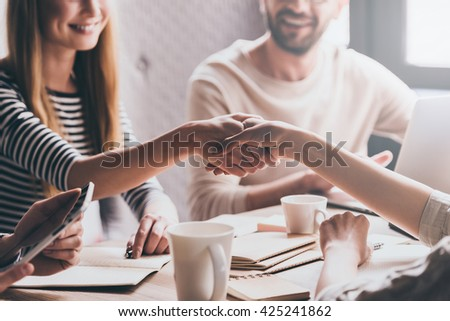 Business handshake. Close-up part of two young women shaking hands with smile while sitting at the business meeting with their coworkers - stock photo