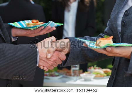 Business handshake during lunch on the open air - stock photo