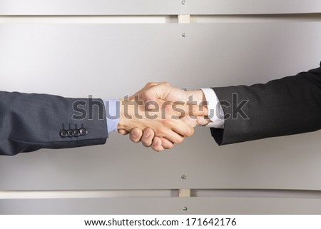 Business handshake on aluminum background